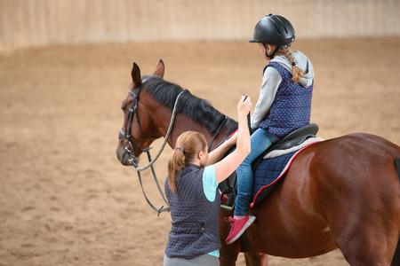 Chica en casco Aprender a caballo. El instructor enseña a adolescente ecuestre.
