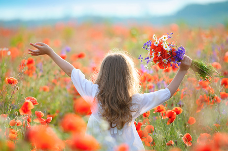 kid girl move thru blooming field with red wild flowers Stockfoto
