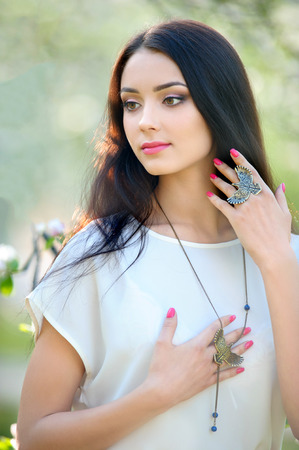 Beautiful woman at the blooming spring garden with stylish ring and necklace.