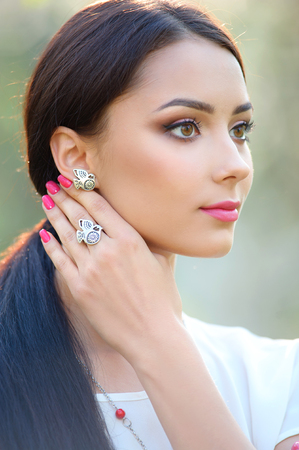 Beautiful young woman with long hair with a beautiful makeup and earring with silver finger ring posing outdoors.