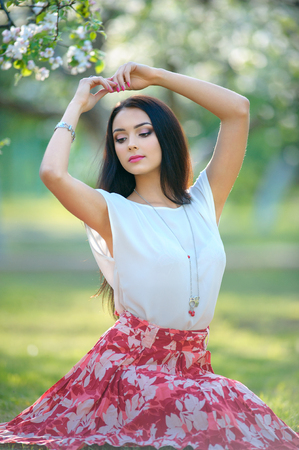 Beautiful model girl with long brown hair posing in blooming spring garden. Woman wearing stylish necklace and bracelet