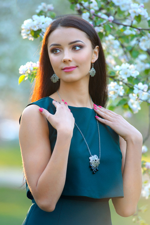 Fashion style woman perfect body shape brunette hair wear elegance dress demonstrated spring collection silver jewelery. Stock Photo