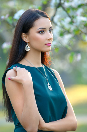 Fashion model beautiful woman wear spring collection luxury accessory and jewelry. Perfect view background blooming garden