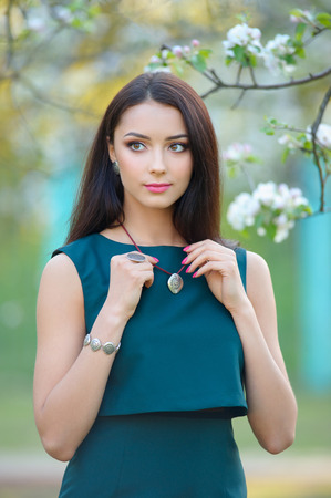 fashion model young woman at blooming spring garden with luxury accessory and jewelry.