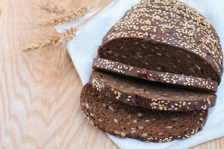 Rye bread with seeds on wooden background, cutout. Whole grain healthy meal Stock Photo