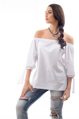 Fashionable young woman wearing Ripped Jeans and white mini dress with silver jewellery  and accessory posing at studio location on white background Stock Photo