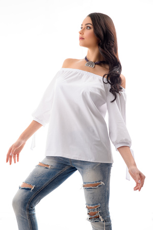 Fashionable looking model wearing Ripped Jeans and jewellery posing sexy at studio location. Banque d'images
