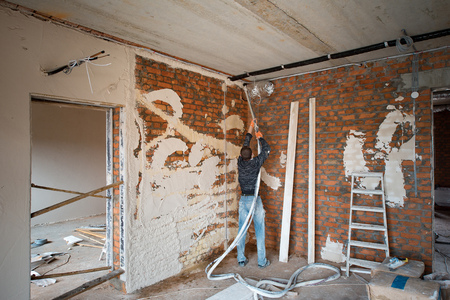 Plastering Walls with a plastering pump Machine Stock Photo