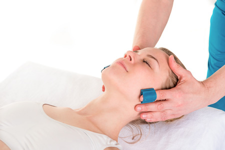 Face skin treatment. Close up shot of a relaxing woman getting face massage in SPA center Stock Photo