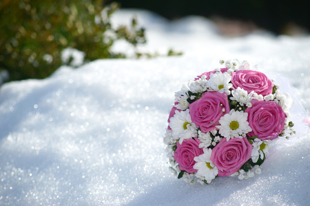 bridal bouquet of pink roses and white daisies flowers in the snow