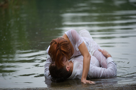 Beautiful young couple making out on the beach, their clothes are wet and the woman is laying on top of the man.