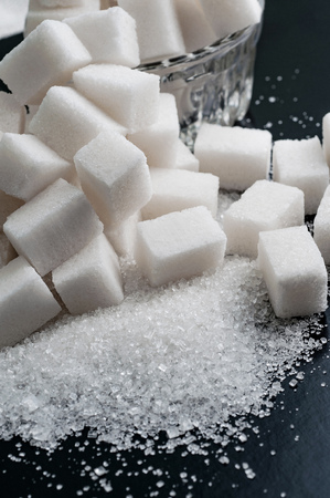 white granulated and refined sugar on black surface, close-up Banco de Imagens