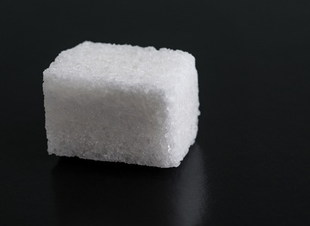 Single Cube of Sugar Isolated on Black Background.