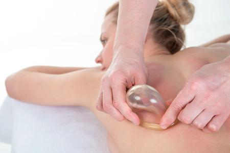 Massage therapist massaging young woman. Vacuum massage, the female body