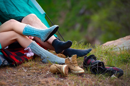 Young Couple lying in a tent. Feet of lying hikers. Camping, travel, tourism, hike and people concept.