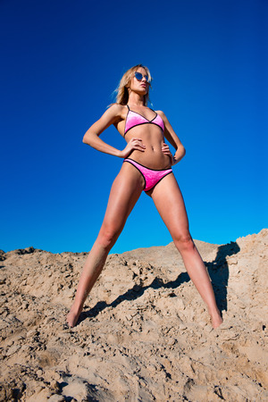 Blonde model woman wearing sunglasses and posing with hands on her stomach. Blue sky and sand background