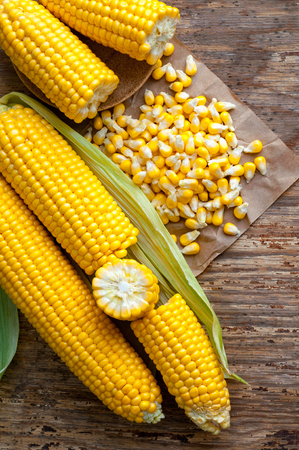 Corn grains on paper with delicious, ripe ears of corn, isolated on wooden background.
