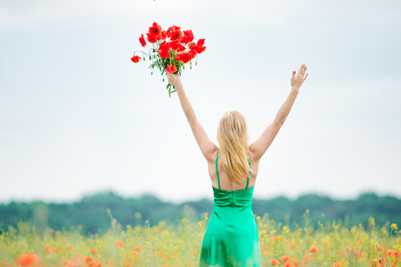 Blonde girl in green dress, on a red poppy meadow with bouquet of beautiful flowers in one hand.