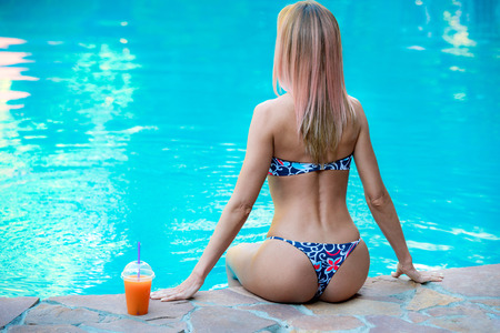 Sexy girl with curvy butt, near the swimming pool, relax and drink juice Stock Photo