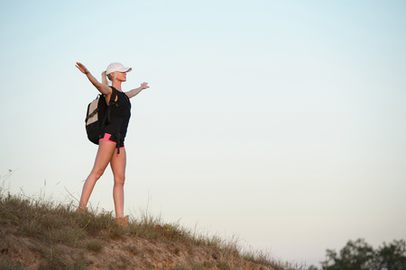 Woman with hands up standing on the top of the hill. Travel, vacation, holidays and adventure concept. Foto de archivo