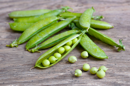 ripe Green peas over wooden background