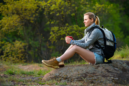 Young woman traveler hiking in summer forest and stopped to have rest with cup of tea. Travel, hiking, backpacking, tourism and people concept Foto de archivo