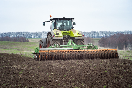 A tractor pulls a disc harrow system implement to smooth over a dirt field in preparation for planting