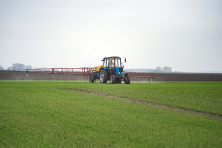 Tractor spraying agrochemical or agrichemical over young grain field Stok Fotoğraf