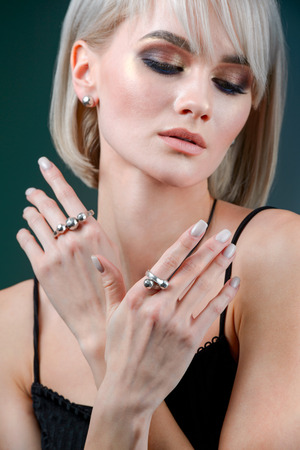 jewelry and fashion concept. Young Model with necklace and rings on a gray background