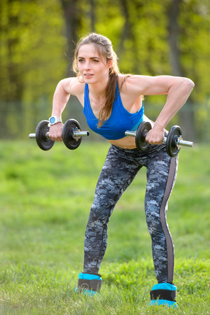 Photo of muscular fitness model working out with dumbbells. Strength and motivation