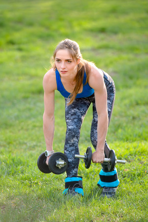 Young Attractive Fitness Woman Doing Dumbbell Exercise on Outdoor
