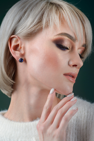 Beautiful blonde with luxurious silver jewelry. Woman wears silver jewelry
