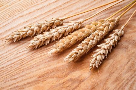ripe wheat ears on wooden background