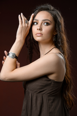 Elegante mujer morena con collares y pendientes de joyería de maquillaje de cabello sano. Hermosa modelo con peinado perfecto