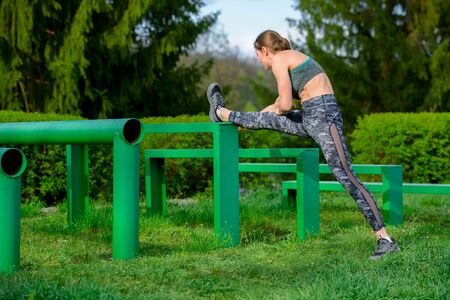 Fitness woman stretch legs, do warm-up before running workout workout outdoor. athlete stretches hamstring muscles Фото со стока