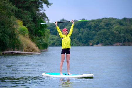 Young  surfer girl standing on a board with a paddle raised up on a background of green trees