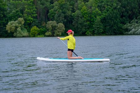 Young girl paddling on SUP board on a calm lake at city. Sup surfing woman. Awesome active training in outdoor.