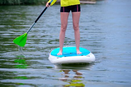 Legs of a young woman standing on a paddle board on the surface of the river. Sports activities. Stand up the paddle. Girl enjoying