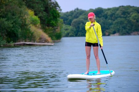young girl-surfer riding on the stand-up paddle board in the clear waters of the on the background of green trees Фото со стока