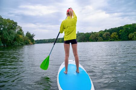 a woman stands on a SUP board on a large river on a cloudy day. Stand on the oars - great outdoor recreation Фото со стока