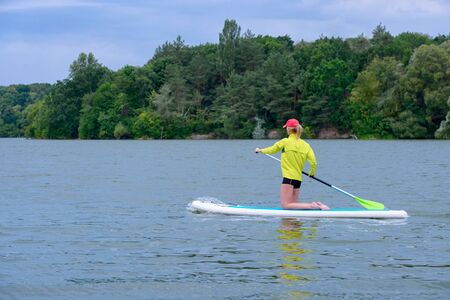 SUP Stand up paddle board concept - Pretty, young woman paddle boarding on a  lake