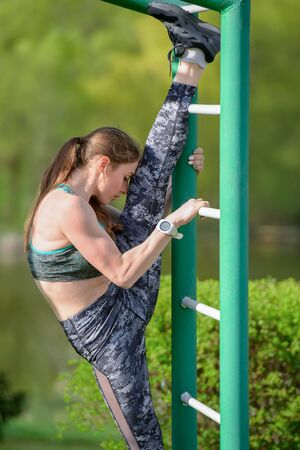 Girl on the street workout. She pulls up her leg on parallel rails. The girl does the splits. She is dressed in a gray T-shirt and gray sweatpants