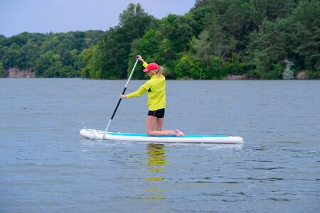 Happy woman resting on the SUP board and enjoying life in the early morning on the big river. Stand on the paddle boarding house - amazing outdoor activities. rear view.