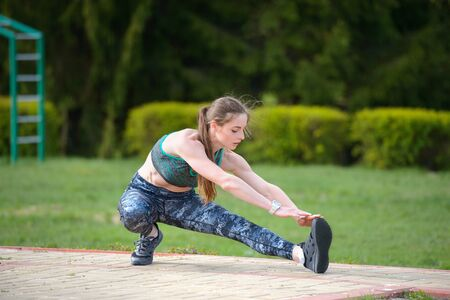 Athletic girl performs hamstring and stretching exercises