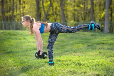 sports girl in a blue tank top with black dumbbells in her hands performs an exercise against the backdrop of summer nature
