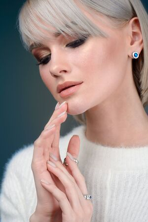 model wearing luxury silver accessory and jewelry. Woman Isolated on blue background Фото со стока