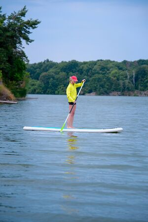 Adult woman swimming on a board. Healthy woman enjoying summer day outdoors.