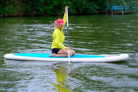 Athletic young woman sitting with a paddle on a river, Active healthy vacation concept Фото со стока