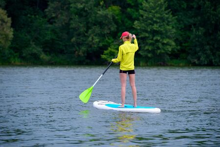Athletic young girl-surfer riding on the stand-up paddle board in the clear waters of the on the background of green trees Фото со стока