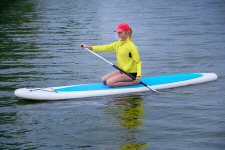 young woman sitting with a paddle on a river, Active healthy vacation concept Фото со стока